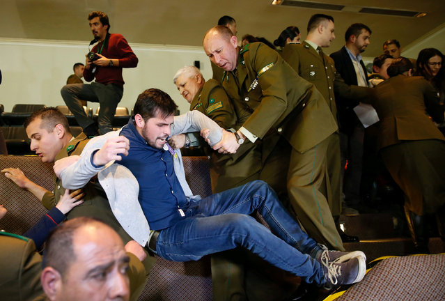 A demonstrator is detained by police officers after shouting slogans against abortion inside the Chilean congress during a session legislating a draft law which seeks to ease the country's strict abortion ban, in Valparaiso, Chile July 18, 2017. (Photo by Rodrigo Garrido/Reuters)