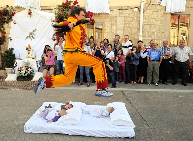 A man representing the devil leaps over babies during the festival of El Colacho in Castrillo de Murcia near Burgos, Spain