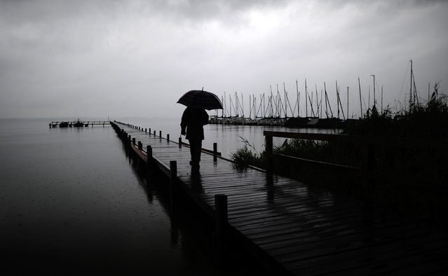 A stroller with umbrella walks on a landing stage  at Lake Steinhuder Meer near Mardorf, northern Germany Friday July 25, 2014. Weather forecasts predict changeable weather for the next few days. (Photo by Alexander Koerner/AP Photo/DPA)
