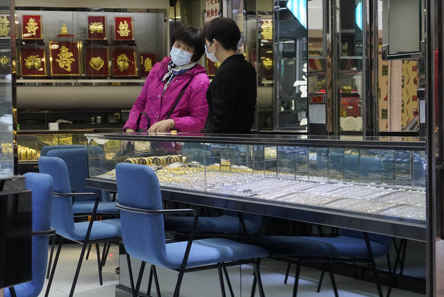 Employees wearing protective face masks at a jewellery shop in Hong Kong, Monday, February 10, 2020. China is reporting a rise in new virus cases, denting optimism that disease control measures which isolated major cities might be working. China reported a rise in new virus cases Monday, possibly denting optimism that disease control measures including isolating major cities might be working, while Japan reported dozens of new cases aboard a quarantined cruise ship. (Photo by Vincent Yu/AP Photo)