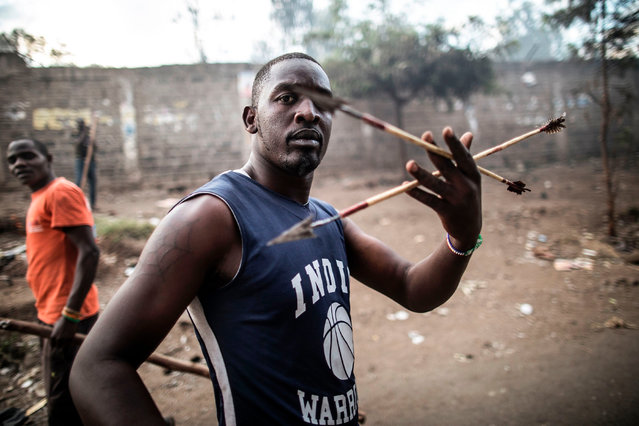 A man brandishes arrows during a street battle between Luo supporters of defeated opposition leader Raila Odinga and members of President Uhuru Kenyatta' s Kikuyu ethnic group, both living in the Mathare slum, on August 13, 2017 in Mathare, a neighborhood of the capital Nairobi. The confrontation broke out after Odinga supporters torched businesses belonging to Kikuyu, who then grouped together armed with sticks, bows and arrows. Clashes followed in which a man was severely beaten, leaving him motionless on the ground. (Photo by Marco Longari/AFP Photo)