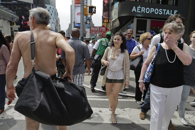 Pedestrians react as George Davis, left, walks nude through Times Square, Wednesday, August 6, 2014, in New York. Davis, a candidate for the San Francisco Board of Supervisors, gave a speech in the nude speaking out against a 2013 San Francisco public nudity ban that was introduced by his opponent, Scott Wiener, saying nudity is a freedom of expression. (Photo by Julie Jacobson/AP Photo)