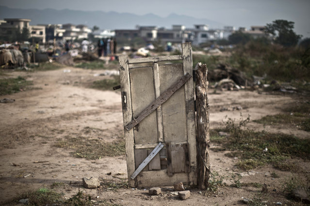 A door of a makeshift home of a Pakistani family is left behind after it was destroyed along with other homes by the Capital Development Authority for being built on illegal lands, in Islamabad, Pakistan, Monday, November 4, 2013. (Photo by Muhammed Muheisen/AP Photo)