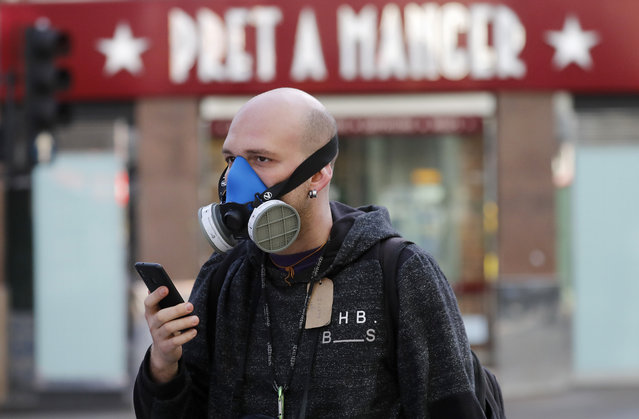 A man wears a mask as he walks through London, Tuesday, March 24, 2020. Britain's Prime Minister Boris Johnson on Monday imposed its most draconian peacetime restrictions due to the spread of the coronavirus on businesses and social gatherings. (Photo by Frank Augstein/AP Photo)