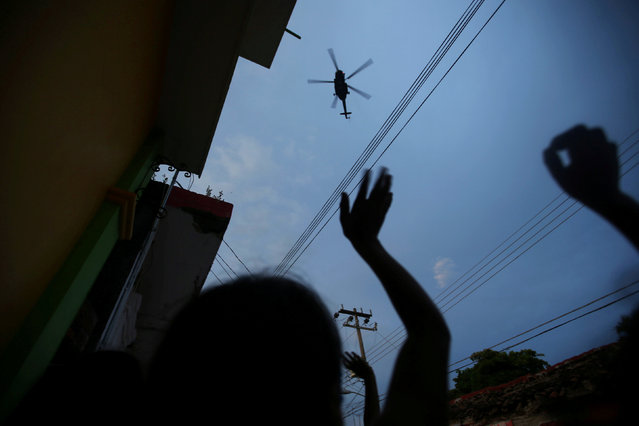 People wave at a helicopter after an earthquake that struck off the southern coast of Mexico late on Thursday, in Juchitan, Mexico, September 9, 2017. (Photo by Edgard Garrido/Reuters)