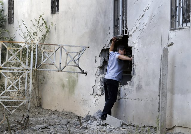 A local citizen inspects the damage after shelling in Donetsk, eastern Ukraine, on August 24, 2014. (Photo by Sergei Grits/AP Photo)