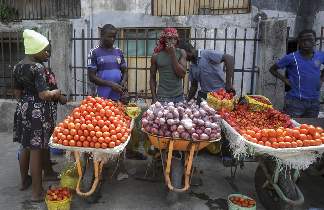 In this April 13, 2020, file photo, a woman buys tomatoes and onions from street sellers in Lagos, Nigeria. Lockdowns in Africa limiting the movement of people in an attempt to slow the spread of the coronavirus are threatening to choke off supplies of what the continent needs the most: Food. (Photo by Sunday Alamba/AP Photo/File)
