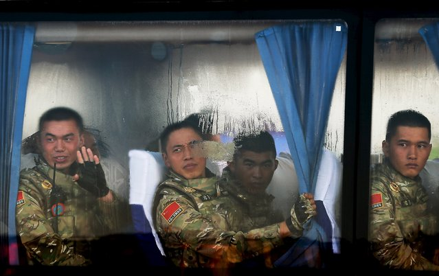 A member of Chinese People's Liberation Army waves while his comrades look out from a bus as they arrive at Tiananmen Gate to take part in a military parade to commemorate the 70th anniversary of the end of World War Two in Beijing, China September 3, 2015. (Photo by Andy Wong/Reuters)