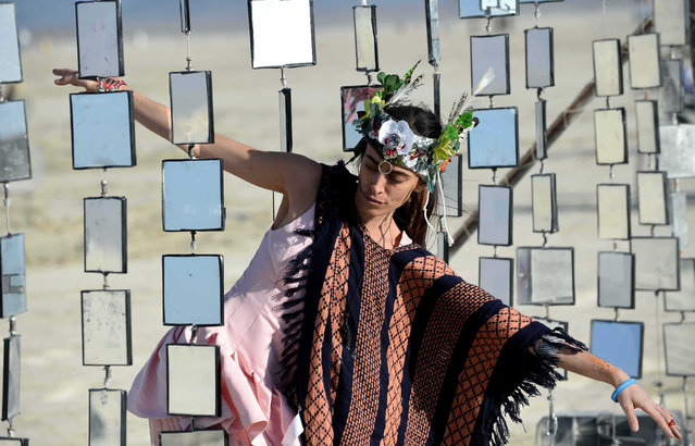 Danielle Petooie of Barzel walks through an art piece at Burning Man on Wednesday, September 2, 2015, in Gerlach, Nev. The Burning Man's theme is Carnival of Mirrors. (Photo by Andy Barron/The Reno Gazette-Journal via AP Photo)