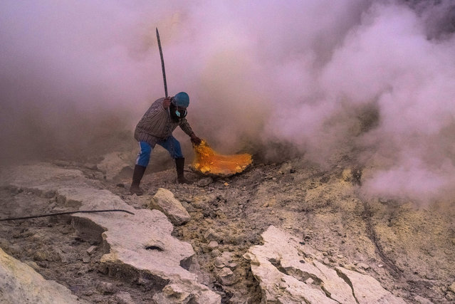 Pipes had been installed at the crater to lead the vaporizing sulfur down to a collecting point, where the miners are cracking the hardened sulfur. Their shift starts at 1 am. Usually it takes them a few attempts because the toxic fumes are swirling unpredictable. Still not all of the miners use gas masks. (Photo by Claudio Sieber/Barcroft Images)