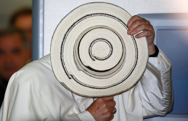 Pope Francis receives a Panama sombrero from a journalist on the plane as he travels from Poland back to Italy, July 31, 2016. (Photo by Stefano Rellandini/Reuters)
