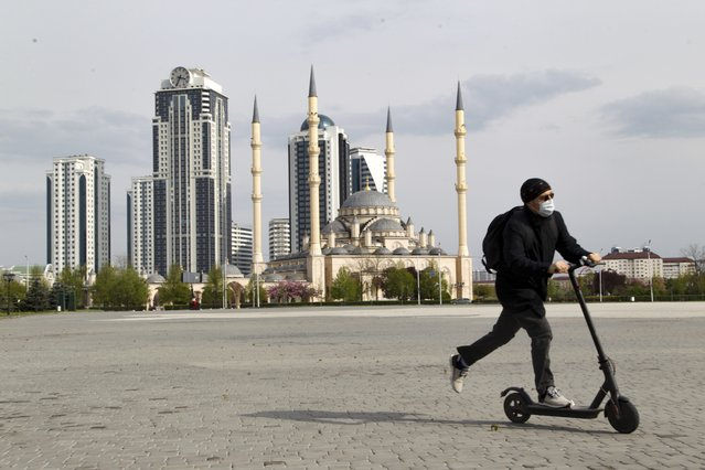 "A man rides a scooter through an empty square in front of closed the Central Mosque ""Heart of Chechnya"" in Grozny, Russia, Thursday, April 23, 2020. Ramadan begins with the new moon later this week as Muslims all around the world are trying to work out how to maintain the many cherished rituals of Islam's holiest month amid the virus pandemic. (Photo by Musa Sadulayev/AP Photo)"