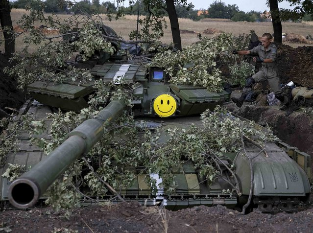 """A Ukrainian soldier jumps to a tank near the eastern Ukrainian town of Pervomaysk September 12, 2014. Ukraine's president said on Friday there could be no military solution to his country's crisis and said he hoped """"a very fragile"""" ceasefire in the east would hold, allowing him to focus on rebuilding the shattered economy. (Photo by Gleb Garanich/Reuters)"""