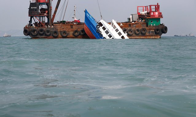 A partially submerged boat is stabilized by the crane of another vessel after it collided with a ferry Monday night near Lamma Island, off the southwestern coast of Hong Kong Island, on October 2, 2012. The boat packed with revelers on a long holiday weekend collided with a ferry and sank off Hong Kong, killing at least 37 people and injuring dozens, authorities said. (Photo by Vincent Yu/AP Photo)