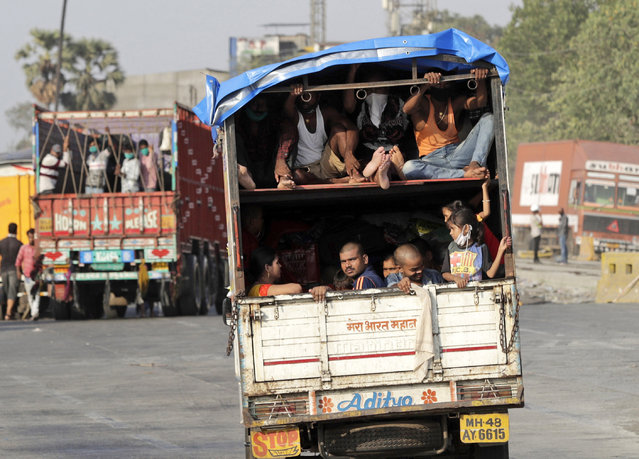 A truck carrying migrant workers leaves for Uttar Pradesh state, on the outskirts of Mumbai, India, Thursday, May 14, 2020. The pandemic has exposed India's deep economic divide as millions of migrant workers have left Indian cities with luggage bags perched on their heads and children in their arms, walking down highways in desperate attempts to reach the countryside. (Photo by Rajanish Kakade/AP Photo)
