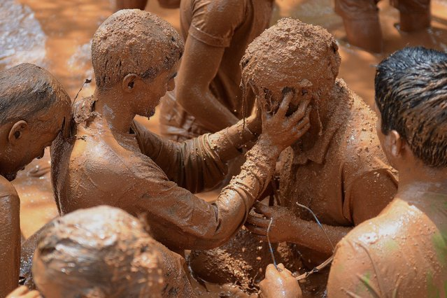 Indian youths participate in the Mudrun on the outskirts of Hyderabad on September 14, 2014. The two kilometre-long run, untimed and with no winners, crossed over muddy obstacles and was organised by the Great Hyderabad Adventure Club (GHAC). (Photo by Noah Seelam/AFP Photo)