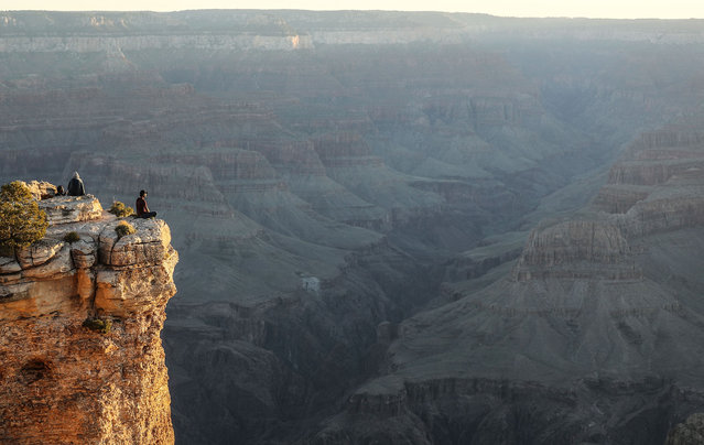 Visitors sit after sunrise on Memorial Day along the South Rim of Grand Canyon National Park, which has partially reopened on weekends amid the coronavirus (COVID-19) pandemic, on May 25, 2020 in Grand Canyon National Park, Arizona. The park has opened for limited hours and access the past two weekends despite concerns that the mingling of visitors could contribute to the spread of the COVID-19 virus.  Critics point out that the neighboring Navajo Nation is currently suffering the highest rate of COVID-19 infection in the nation per capita and some travelers would need to pass through the nation to arrive at the park. (Photo by Mario Tama/Getty Images)