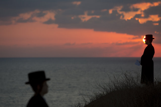 "Ultra-Orthodox Jews of the Hassidic sect Vizhnitz gather on a hill overlooking the Mediterranean sea as they participate in a Tashlich ceremony in Herzeliya, Israel, Thursday, October 2, 2014. Tashlich, which means ""to cast away"" in Hebrew, is the practice by which Jews go to a large flowing body of water and symbolically ""throw away"" their sins by throwing a piece of bread, or similar food, into the water before the Jewish holiday of Yom Kippur, which start on Friday. (Photo by Oded Balilty/AP Photo)"