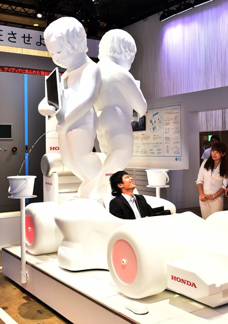 Two large replicas of the famous statue Manneken Pis, standing on the engine space of a model of a F1 machine, to display an explanation of fuel cell systems at Japanese automaker Honda booth at the CEATEC electronics trade show in Chiba, suburban Tokyo on October 7, 2014. (Photo by Yoshikazu Tsuno/AFP Photo)