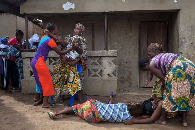 Women faint (Bottom) as another reacts while volunteers (unseen) take away from a nearby house the body of a woman who died of Ebola, in Waterloo, some 30 kilometers southeast of Freetown, on October 7, 2014. Dozens of British military personnel are due to fly to Sierra Leone next week to help build medical facilities to combat the Ebola epidemic, the defence ministry said on October 7. (Photo by Florian Plaucheur/AFP Photo)