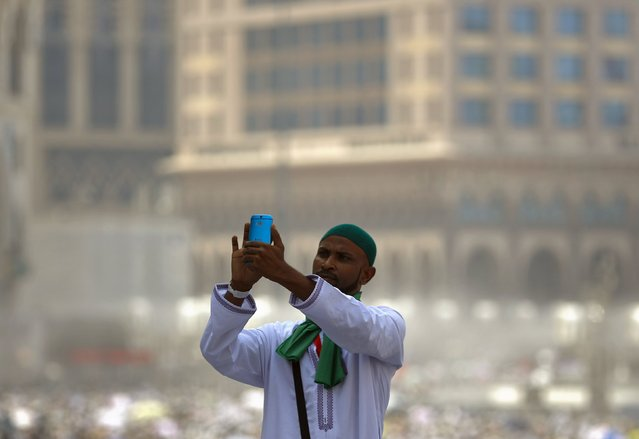 A Muslim pilgrim uses his mobile phone to take picture after Friday prayers outside the Grand mosque in the holy city of Mecca ahead of the annual haj pilgrimage September 18, 2015. (Photo by Ahmad Masood/Reuters)