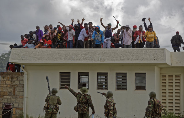 Police order supporters of President Uhuru Kenyatta off a roof during clashes at his inauguration ceremony after they tried to storm through gates to get in and were tear-gassed, at Kasarani stadium in Nairobi, Kenya Tuesday, November 28, 2017. (Photo by Ben Curtis/AP Photo)
