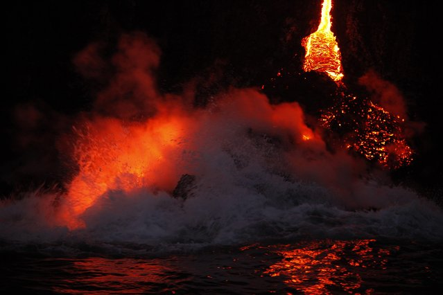 Waves crash over lava as it flows into the ocean near Volcanoes National Park in Kalapana, Hawaii on November 27, 2012. A volcano on Hawaii's largest island is spilling lava into the ocean, creating a rare and spectacular fusion of steam and waves that officials said on Tuesday could attract thrill seeking visitors if it continues. (Photo by Hugh Gentry/Reuters)