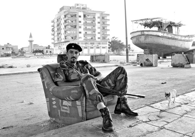 """Libyan Rebel at the Old Shipyard of Benghazi: During the Libyan revolt against Moammar Qaddafi, the city of Benghazi was liberated early on, and became the base for the rebels and the transitional governing body. Armed rebels were seen all over the place. Many of them had no previous war experience but joined the revolt willingly to get rid of the regime. This rebel, with his spick & span boots and outfit, was guarding the old shipyard"". (Photo and comment by Mohannad Khatib/National Geographic Photo Contest via The Atlantic)"
