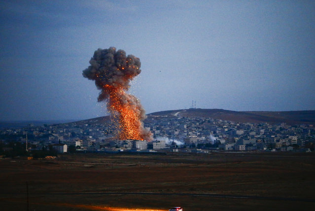 Smoke rises over Syrian town of Kobani after an airstrike, as seen from the Mursitpinar border crossing on the Turkish-Syrian border in the southeastern town of Suruc in Sanliurfa province, October 18, 2014. (Photo by Kai Pfaffenbach/Reuters)