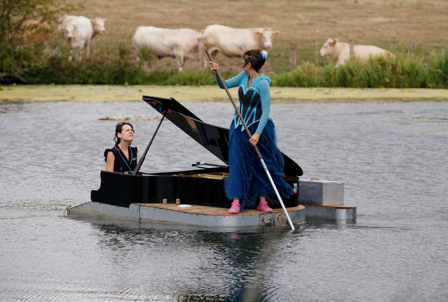"Pianist Cecile Wouters and singer Evelyne Zou perform on a lake during a rehearsal of their show ""Melting Flotte"" at the Chateau de Ricquebourg in Ricquebourg, France on July 24, 2020. (Photo by Pascal Rossignol/Reuters)"