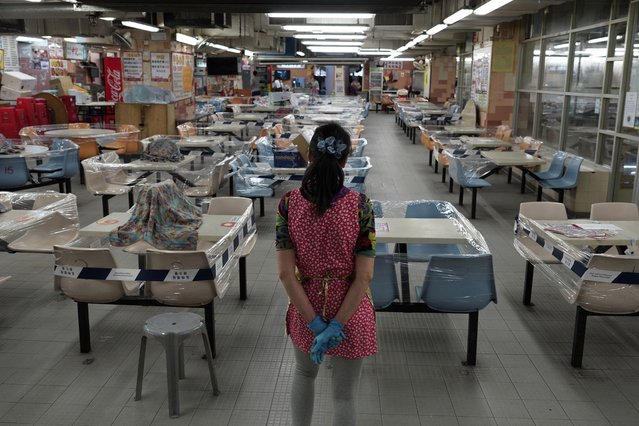 A restaurant employee looks at empty sits at a Chinese food court in Hong Kong, Wednesday, July 29, 2020. Hong Kong has banned dining-in at restaurants completely on Wednesday and make it mandatory to wear masks in all public places, as the city battles its worst coronavirus outbreak to date. (Photo by Vincent Yu/AP Photo)