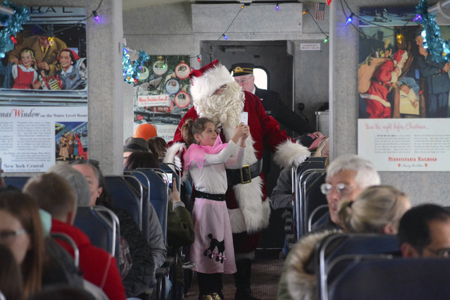 Dressed in 1950's garb, Margot Nelson 8, of Princeton, Mass. takes a selfie with Santa on the Tinseliner, the Berkshire Scenic Railway's Hoosac Valley Train Line between the towns of Adams and North Adams, Mass. on Sunday, December 17, 2017. (Photo by Gillian Jones/The Berkshire Eagle via AP Photo)