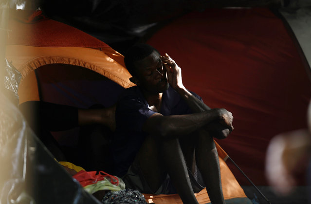 An African migrant stranded in Costa Rica sits outside his camping tent in a makeshift camp at the border between Costa Rica and Nicaragua, in Penas Blancas, Costa Rica, September 8, 2016. (Photo by Juan Carlos Ulate/Reuters)