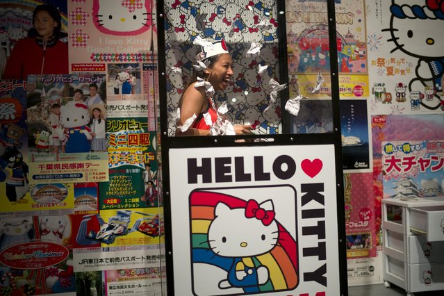Alyssa Lopez, of San Diego, Calif., plays the money grab game at the Hello Kitty Con, the first Hello Kitty fan convention, held at the Geffen Contemporary at MOCA Thursday, October 30, 2014, in Los Angeles. (Photo by Jae C. Hong/AP Photo)
