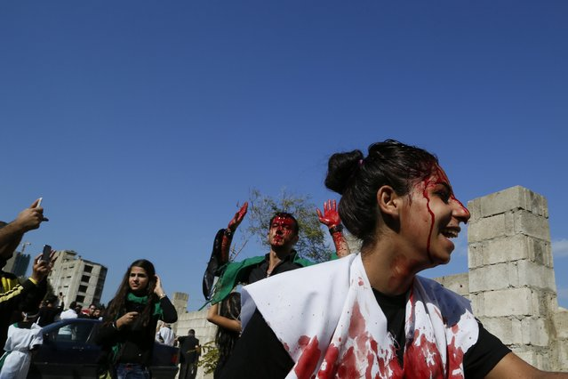A Shi'ite Muslim girl marches with men, who are bleeding after tapping their foreheads with razors during the Ashoura ceremony held in Beirut November 4, 2014. Ashoura, which falls on the 10th day of the Islamic month of Muharram, commemorates the death of Imam Hussein, grandson of Prophet Mohammad, who was killed in the seventh century battle of Kerbala. (Photo by Jamal Saidi/Reuters)