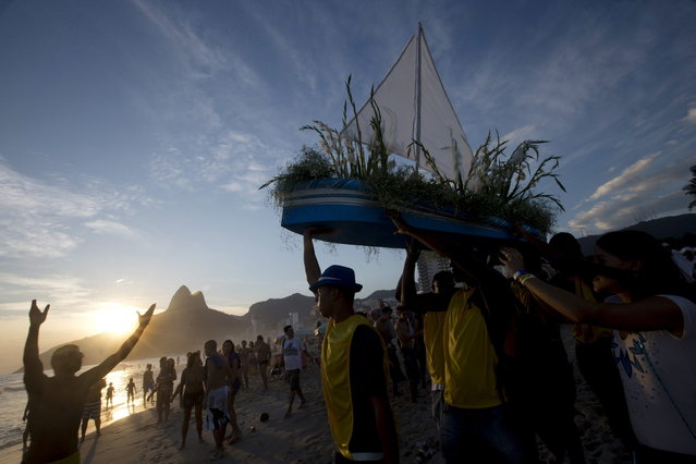 "Simpatia e Quase Amor or ""Kindness is almost love"", block party members and faithful carry a boat filled with flowers as an offering to the sea goddess,Yemanja, during a pre-Carnival celebration in Rio de Janeiro, Brazil, Saturday, February 2, 2013. Worshippers honor the deity, offering flowers and launching boats, large and small, into the ocean showing their gratitude for her blessings bestowed upon them. The belief in the goddess comes from the African Yoruban religion brought to America by West African slaves. (Photo by Silvia Izquierdo/AP Photo)"