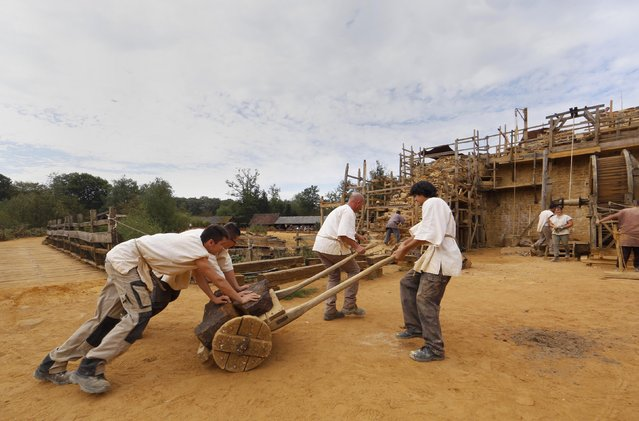 Workers carry stones at the construction site of the Chateau de Guedelon near Treigny in the Burgundy region of France, September 13, 2016. (Photo by Jacky Naegelen/Reuters)