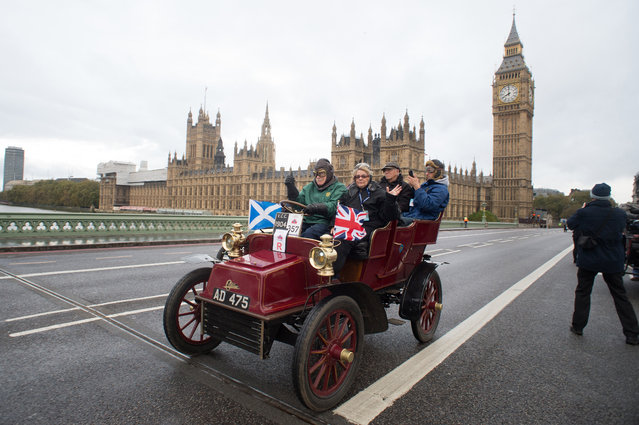 Participants drive their car over Westminster Bridge in the London to Brighton Veteran Car Run in London, England, Sunday, November 2, 2014, with the Houses of Parliament in the background. Hundreds of pre-1905 manufactured vehicles made their way on the historic 60-mile run from Hyde Park in London to coastal Brighton in southern England, in the world's longest running motoring celebration spanning 118 years. (Photo by Tim Ireland/AP Photo)
