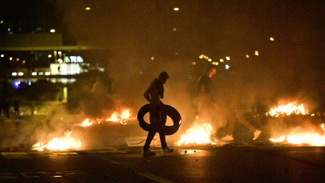 Demonstrators burn tyres during clashes with police in the Rosengard neighbourhood of Malmo, Sweden, on August 28, 2020. The protest was sparked by the burning of a coran by members of Danish far-right party Stram Kurs during an anti-Muslim rally in Malmo earlier in the day. The party's leader Rasmus Paludan, known for his anti-Muslim rhetoric, was due to attend the rally but he was arrested near Malmo and has been banned from Sweden for two years, authorities said on August 28. (Photo by TT News Agency via AFP Photo)