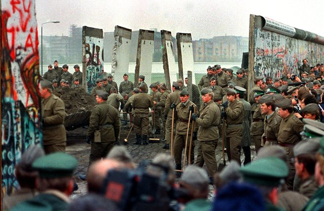 East German soldiers and West German soldiers remove some of the first sections of the Berlin Wall at Potsdammer Platz on November 11, 1989. (Photo by John Tlumacki/The Boston Globe via Getty Images)