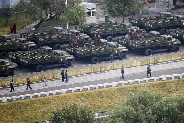 People pass by soldiers and their vehicles lined up on banks of Taedong River before the start of a parade celebrating the 70th anniversary of the founding of its ruling Workers' Party of Korea, in Pyongyang, North Korea October 10, 2015. (Photo by Damir Sagolj/Reuters)
