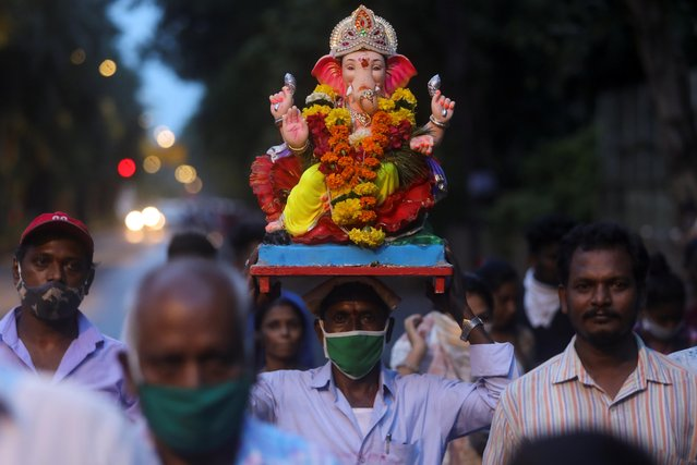 People wearing protective masks carry an idol of the Hindu god Ganesh, the deity of prosperity, for immersion off the coast of the Arabian sea during the Ganesh Chaturthi festival in Mumbai, India, August 23, 2020. (Photo by Francis Mascarenhas/Reuters)