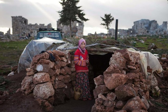 A Syria girl stands at the entrance of a makeshift home set up in the catacombs of the ruins of an ancient building in the ancient Roman city of of Serjilla, in northwestern Syria, on February 11, 2013, after fleeing the fighting between rebel forces and pro-government troops in the town of Kfar Nubul,  in the northwestern province of Idlib. (Photo by Daniel Leal-Olivas/AFP Photo)