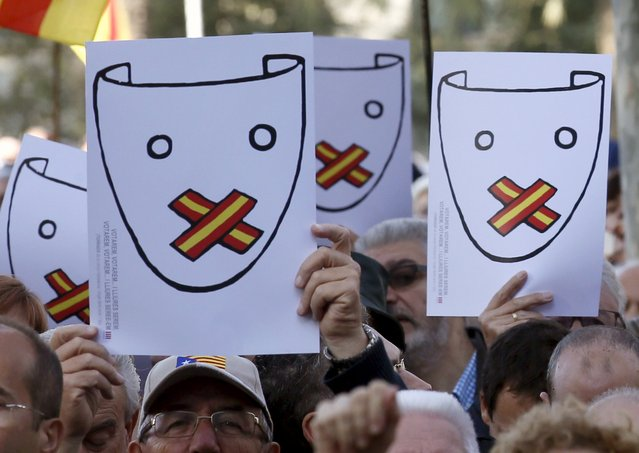 People show placards supporting Catalonian President Artur Mas (not in picture) at his arrival to appear in court after being indicted by his region's supreme court for pushing ahead with the symbolic referendum on independence that took place on November 9, 2014, in Barcelona, Spain, October 15, 2015. (Photo by Albert Gea/Reuters)