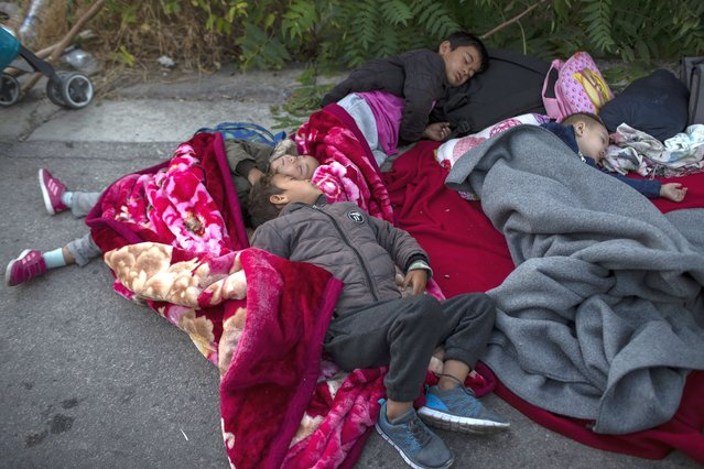 Migrants sleep on the road near the Moria refugee camp on the northeastern island of Lesbos, Greece, Thursday, September 10, 2020. A second fire in Greece's notoriously overcrowded Moria refugee camp destroyed nearly everything that had been spared in the original blaze, Greece's migration ministry said Thursday, leaving thousands more people in need of emergency housing. (Photo by Petros Giannakouris/AP Photo)
