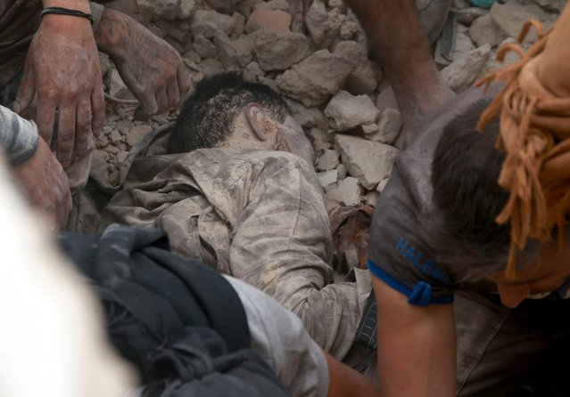 Syrians try to rescue a dead body under the debris of a collapsed building after Syrian and Russian army carried out an airstrike on opposition controlled residential area at Merce neighborhood of Aleppo, Syria on September 23, 2016. (Photo by Jawad al Rifai/Anadolu Agency/Getty Images)