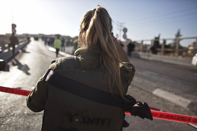An Israeli soldier looks on at the scene of a stabbing attack in the West Bank Jewish settlement of Adam, north of Jerusalem October 21, 2015. On Wednesday, Israeli forces shot dead a Palestinian who stabbed and wounded a soldier near the Jewish settlement of Adam in the occupied West Bank, police said. (Photo by Nir Elias/Reuters)