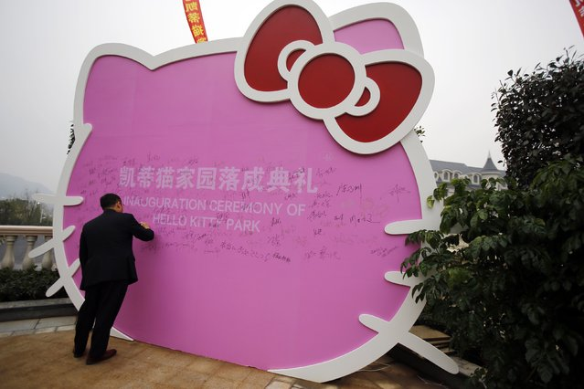 A man signs on a Hello Kitty cut-out during an inauguration ceremony of a Hello Kitty amusement park in Anji, Zhejiang province November 28, 2014. (Photo by Carlos Barria/Reuters)