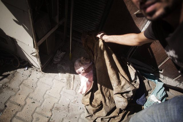 The body of an elderly man, said by rebels to be a Coptic Christian, lies at the door of a hospital controlled by the Free Syrian Army in Aleppo, Syria, Wednesday, September 19, 2012. (Photo by Manu Brabo/AP Photo)