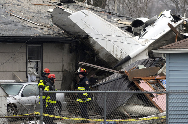South Bend firefighters work at the scene, Monday, March 18, 2013, where a plane crashed on Sunday, near the South Bend Regional Airport, in South Bend, Ind. The plane damaged homes, as well as causing injuries. (Photo by Joe Raymond/AP Photo)
